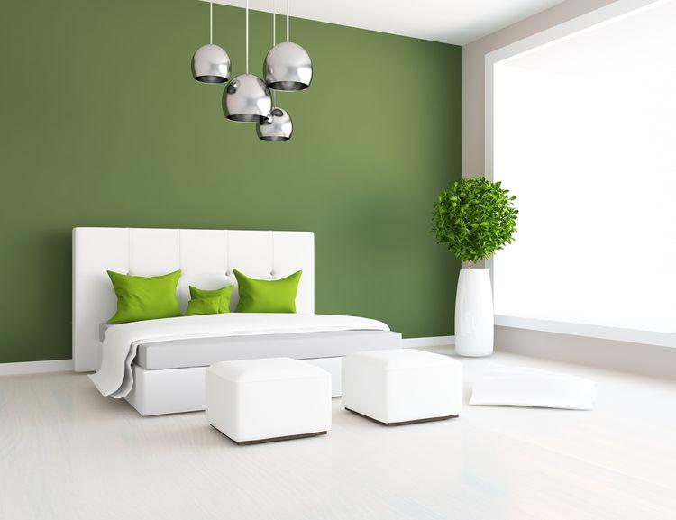 Tmavě zelená stěna a polštáře v ložnici