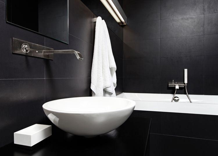 Černá koupelna s bílým umyvadlem
