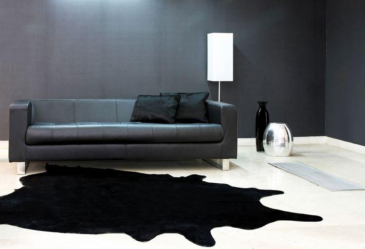 Černý gauč, koberec a stěna