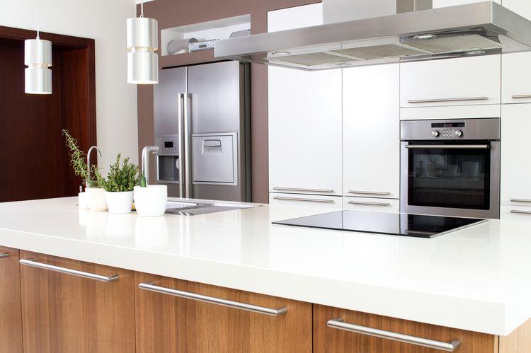 Bílá kuchyň s hnědým kuchyňským ostrůvkem