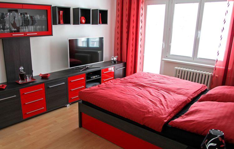 Šedo-červený lesklý nábytek a postel s červenými peřinami