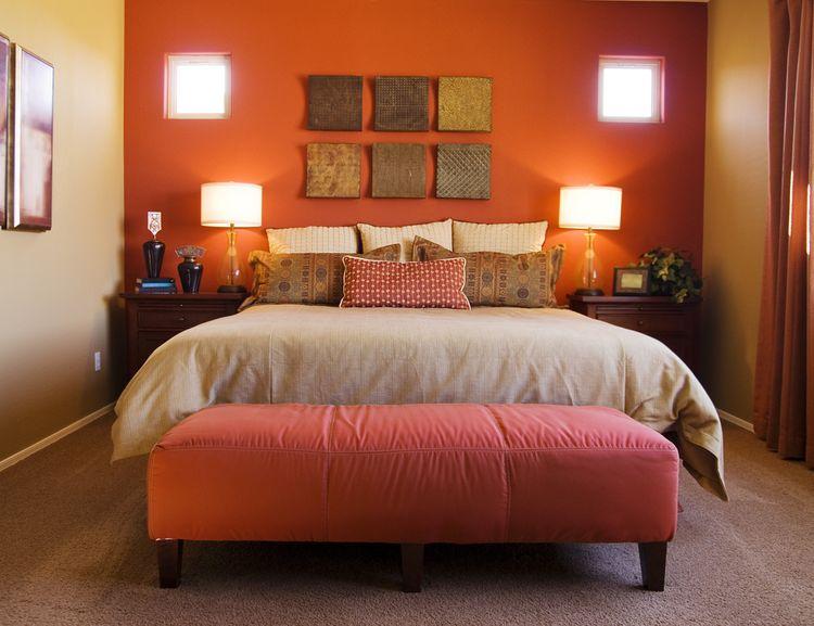 Ložnice s matnou červenou stěnou a velkou postelí