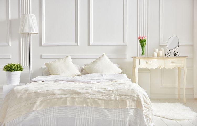 Ložnice s bílou postelí a stěnami