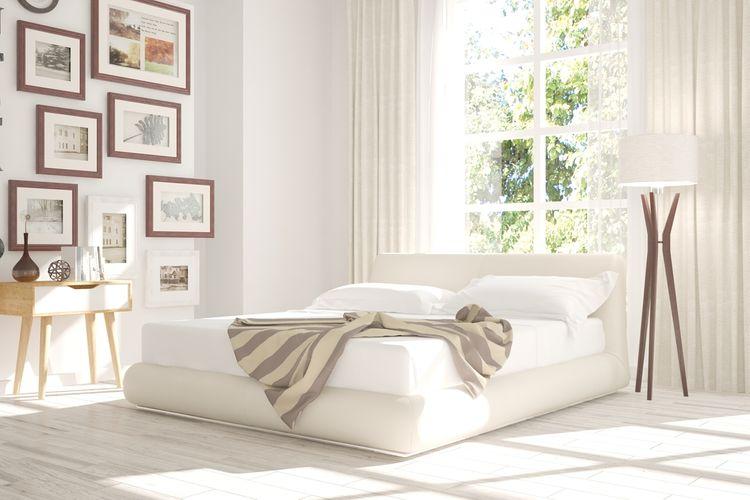 Minimalistická ložnice s bílou postelí, dřevěným stolkem a obrazy