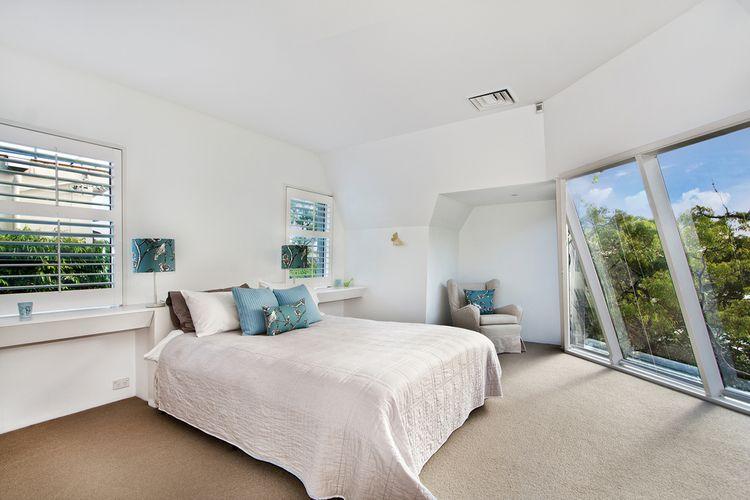 Moderní podkrovní bílá ložnice s modrými detaily