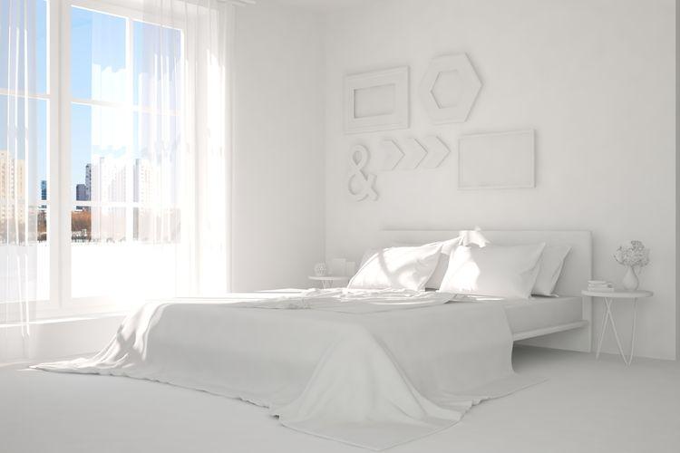 Ložnice s bílými postelí, stěnami a obrazy